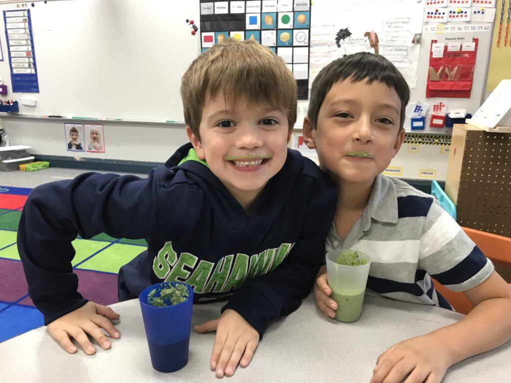 Two kids enjoying green smoothie