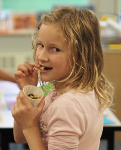 Girl enjoying eating a tasting of kale salad