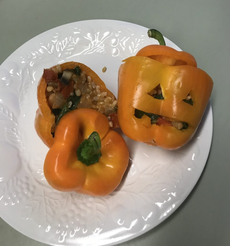 Two jack o lantern stuffed bell peppers on plate