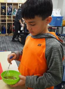 Boy whisking salad dressing for a salad