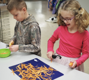 A boy and a girl using a peeler to cut carrots