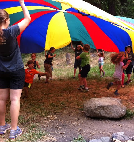 Kids under parachute at camp