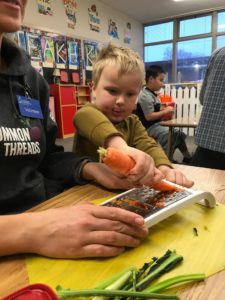Student chef is learning to shred carrots