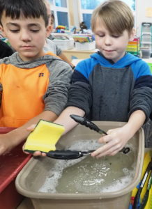 Two kids washing dishes in a classroom