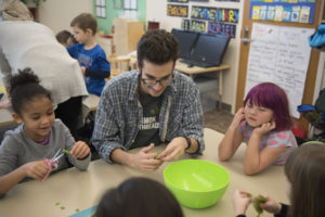 Common Threads Volunteer Daniel Murphy assisting with a cooking lesson
